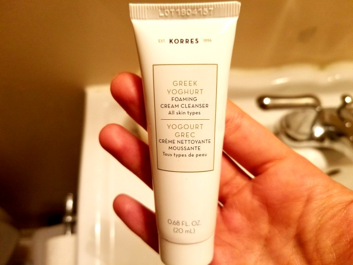 Photo of the the sample size of the Korres Greek Yoghurt Foaming Cream Cleanser inside my open palm. It's a white, palm-sized squeeze container with a light pink rectangle where the text appears. :)